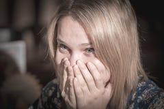 Jovem mulher surpreendida que cobre sua boca com as mãos fotografia de stock royalty free