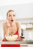 Jovem mulher surpreendida que come a pipoca e que olha a tevê na cozinha fotografia de stock