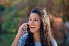 Jovem mulher surpreendida que fala no telefone no parque Imagens de Stock
