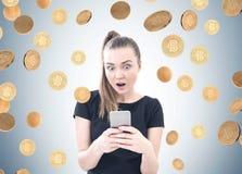 Jovem mulher surpreendida, smartphone, chuva do bitcoin imagem de stock royalty free
