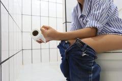 A jovem mulher tem a constipação ou as hemorroidas que sentam-se no toalete, conceito saudável fotos de stock