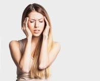 A jovem mulher tem a dor de cabeça, em um fundo cinzento Imagem de Stock Royalty Free