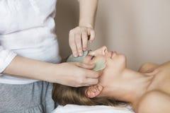 A jovem mulher tem o tratamento da cara na clínica da beleza foto de stock royalty free