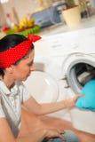 A jovem mulher tem um dia da lavanderia em casa Foto de Stock