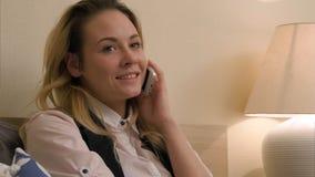 A jovem mulher tem uma conversação positiva usando o telefone celular que senta-se na cama Imagem de Stock Royalty Free