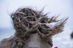 A jovem mulher temperamental no vestido vermelho tem o divertimento no penhasco da costa de mar foto de stock royalty free