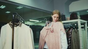 A jovem mulher tenta sobre a roupa na loja da roupa filme