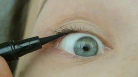 A jovem mulher tira setas usando o lápis de olho Composição natural do olho em casa vídeos de arquivo