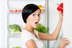 A jovem mulher toma a pimenta vermelha do refrigerador aberto Imagens de Stock