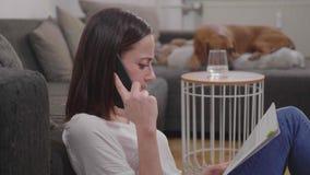 A jovem mulher toma um telefonema ao classificar documentos filme