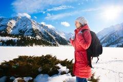 A jovem mulher toma uma caminhada na inclinação de montanha do inverno (LAK grande de Almaty Fotos de Stock