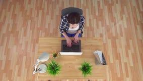 A jovem mulher trabalha atrás da opinião superior do portátil vídeos de arquivo