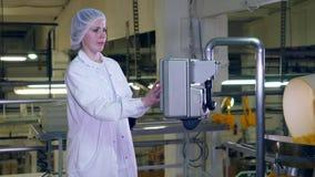 A jovem mulher trabalha com equipamento da fábrica em uma facilidade de produção alimentar filme