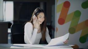 A jovem mulher trabalha com originais e as respostas chamam o escritório interno vídeos de arquivo
