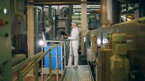 A jovem mulher trabalha em uma fábrica do alimento, datilografando em um portátil filme