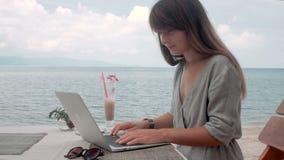 A jovem mulher trabalha no portátil no café exterior, câmera movente, tiro do estabilizador filme