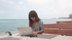 A jovem mulher trabalha no portátil no café exterior, girando o tiro do estabilizador da câmera video estoque