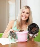 A jovem mulher transplanta flor potted Foto de Stock Royalty Free