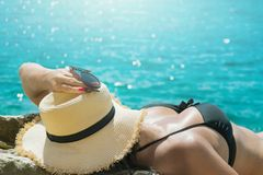 Jovem mulher traseira da vista no chapéu preto do roupa de banho e de palha na praia selvagem do snone com mar limpo imagens de stock