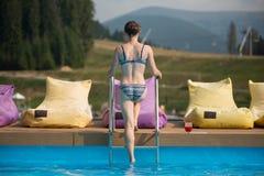Jovem mulher traseira da vista que sai da água de uma piscina no recurso, perto dos suportes um o vidro com uma bebida foto de stock royalty free