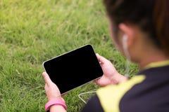 Jovem mulher traseira da vista que senta-se no campo de grama e que joga a tabuleta Imagens de Stock