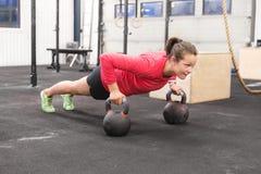 A jovem mulher treina flexões de braço com kettlebells Imagem de Stock
