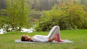 A jovem mulher treina suas mãos ao encontrar-se em uma esteira da ioga em um banco de rio video estoque