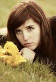 Jovem mulher triste com as flores que encontram-se na grama Fotografia de Stock Royalty Free