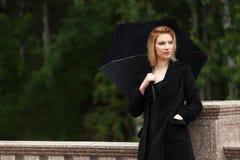 Jovem mulher triste com o guarda-chuva na chuva foto de stock