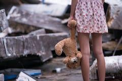 Jovem mulher triste que está e que guarda sua boneca do urso em sua mão esquerda fotografia de stock royalty free