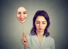 Jovem mulher triste que olha abaixo de descolar a máscara feliz dsi mesma foto de stock royalty free