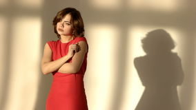 A jovem mulher triste Unsmiling pôs suas mãos sobre templos A menina bonita abraça-se na sala Senhora In Red Há ela vídeos de arquivo