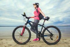 jovem mulher, um atleta nas sapatas cor-de-rosa, caminhadas com um Mountain bike Fotos de Stock