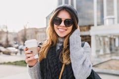 Jovem mulher urbana elegante do retrato com o caf? para ir andar no centro de cidade ensolarado Menina de sorriso de surpresa em  fotos de stock