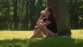 A jovem mulher usa fones de ouvido e bebe o café video estoque