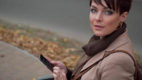 A jovem mulher usa o smartphone ao sentar-se no banco na cidade filme