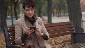 A jovem mulher usa o smartphone ao sentar-se no banco na cidade vídeos de arquivo
