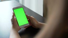 A jovem mulher usa o smartphone com greenscreen para uma comunicação video estoque