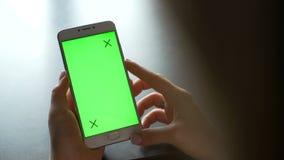 A jovem mulher usa o smartphone com greenscreen para uma comunicação vídeos de arquivo