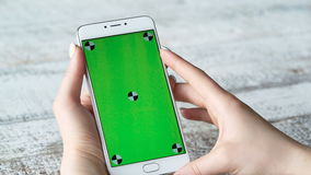 A jovem mulher usa o smartphone com tela verde vídeos de arquivo