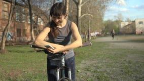 A jovem mulher usa o telefone ao guardar sua bicicleta vídeos de arquivo