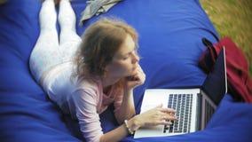 A jovem mulher usa um portátil, encontrando-se em uma área da sala de estar do parque em sopros macios vídeos de arquivo