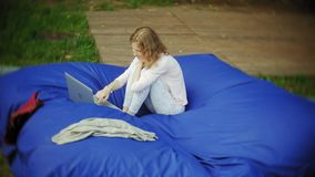 A jovem mulher usa um portátil, encontrando-se em uma área da sala de estar do parque em sopros macios video estoque