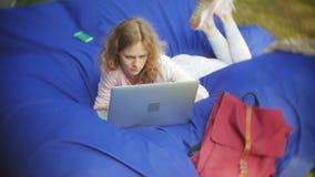 A jovem mulher usa um portátil, encontrando-se em uma área da sala de estar do parque em sopros macios filme