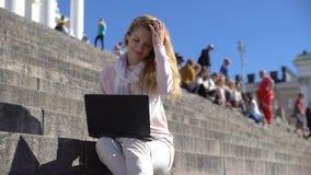 A jovem mulher usa um portátil nas escadas no centro da cidade video estoque