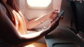 A jovem mulher usa um smartphone durante um voo do avião filme