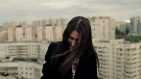 A jovem mulher usa um smartphone no telhado filme