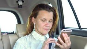 A jovem mulher usa um telefone celular no carro vídeos de arquivo