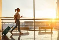 A jovem mulher vai no aeroporto na janela com a mala de viagem que espera imagens de stock royalty free
