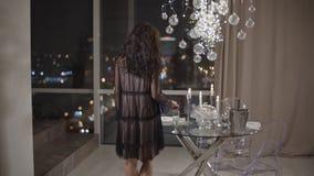 A jovem mulher vem à janela com uma vista espetacular de uma cidade da noite filme